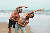 Healthy sport man and women stretching body warm up before workout outdoor. Two Athlete in sportswear happy nice resting at the beach. Exercise to prevent the coronavirus and New normal concept