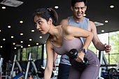 The personal trainer helps Asian women with one arm triceps workout in fitness gym. Concepts of exercise for health and good shape. cinematic tone