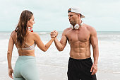 Man and woman in sportswear holding hands after the running training at the beach. Fit couple high five after outdoor exercise.