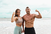 Portraits of Cheerful male and female athlete standing together at seaside. Healthy men and women pose for sexy poses and show off their muscles in the summer day.