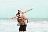 Happy couple in sport wear on vacation at tropical city. Man and woman Lovers enjoy each other in the beach after outdoor workout training. man carrying girlfriend on his back along the seaside