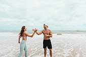 Man and woman in sportswear giving five after the running training at the beach .Fit couple high five after outdoor exercise.