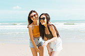 Two Asian women friends in summer casual clothes Take a photo together at the beach on vacation in tropical country. Young beautiful Female joy in the beach on a sunny day