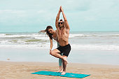 Couple practicing yoga together on the beach at the summer day.  Man and woman exercise stretching body at seascape with he professional instructor. Yoga flexibility class workout.