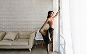 A beautiful Asian woman's fitness at home instead of going to the fitness gym. She warms up the body stretching legs in the white room. She wears sportswear. Exercise concept for good shape