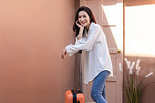 Asian woman posing in trendy look. Portrait of a smiling brunette women natural makeup wear fashion clothes going to travel. Beautiful female model wearing a big white shirt. people beauty concept.