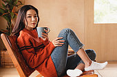 Portrait of a young Asian woman wearing a sweater. She inhaled the scent and drank the winter morning coffee. She smiles and enjoys being relaxed at home.