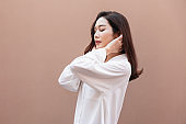 Young asian woman posing in trendy look. Portrait of a smiling brunette women natural makeup wear fashion clothes. Beautiful female model wearing a big white shirt. people beauty concept.