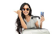 A portrait of an Asian woman wearing a summer dress with a suitcase. She is holding a credit card and point to the side space. She presents the travel promotion. Isolated on white background