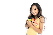 Portrait of an Asian woman carrying many green and red apples. Body care and weight loss concept. Isolated on white background