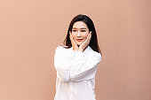 Asian woman clean fresh skin posing in trendy look. Portrait of a smiling brunette women natural makeup smiling after fantastic face treatment. Skin care and beauty concept.