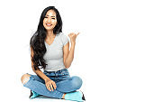 A young Asian woman wore a casual dress sit on the floor. She pointed her finger to the side space. Isolated on white background. Isolated on white background