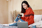 portrait of a young beautiful sexy Asian woman wearing a sweater at home. A professional female photographer checks photos on the camera