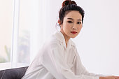 Asian woman clean fresh skin posing in trendy look. Portrait of a brunette model with bright makeup with red lips. Skin care and fashion beauty concept.