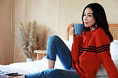 close up portrait of a young beautiful Asian woman wearing a sweater at home. She drinks hot coffee in bed in the morning. She felt relaxed in the sunny form window.