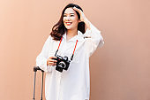 Asian woman posing in trendy look Taking photos while travel on summer day. Portrait of a smiling brunette women natural makeup wear fashion clothes . female traveler drag the suitcase