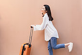 Asian woman posing in trendy look. Portrait of a smiling brunette women natural makeup wear fashion clothes going to travel on summer day. female traveler wearing a big white shirt drag the suitcase