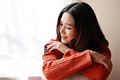 close up portrait of a young beautiful Asian woman wearing a sweater at home. She felt relaxed in the room with the morning sunny.