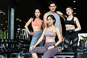 A group of beautiful and handsome young Asian people standing and taking pictures together after exercising in the gym. They look at the camera.Group Shot