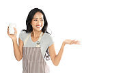 Portrait of an Asian woman wearing an apron holding a coffee cup. She looked at the copy space and opened the palm to present the promotion. Isolated on the white background