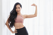 A beautiful Asian women's fitness at Home instead of going to the fitness gym.Her showing muscles of the arm in the White room. She has a smiling face and wears sportswear. Exercise for good shape5