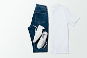 White t-shirt, blue jeans and white sneakers on white background