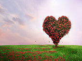 Tree of love in spring. Red heart shaped tree at sunset. Beautiful landscape with flowers.Love background