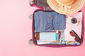 suitcase bag with clothing and mask on pink background. summer vacation travel with coronavirus pandemic.