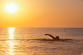 strong man swimming in sea at sunrise