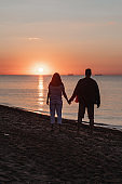 couple holding hands looking at sunset above sea