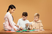 happy children cutting colored papers with scissors