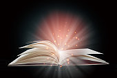 Open white paper fantasy book with shining pages isolated on black background