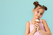 cute little girl eating vanilla ice cream in waffle cone