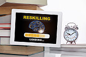 Reskilling loading with brain on digital computer tablet with stack of textbook with time to change words on alarm clock isolated on white background