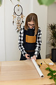 florist woman cutting paper on table with plants.