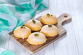 Lemon shaped citrus flavored cake coated with sugar sweet icing and  pistachio