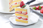 Strawberry and cream sponge cake on white wooden table