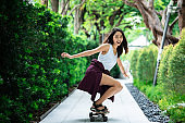 Asian young women surf skate or skates board outdoors on beautiful summer day. Happy young women happy play surf skate  at rooftop city bangkok.