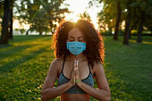 Staying healthy during coronavirus outbreak. Young mixed race woman wearing protective face mask meditating and practicing yoga outdoors during covid 19 pandemic
