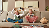 Two cute siblings, little boy and girl playing video games, sitting on a couch in the living room