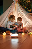 Two adorable little kids, brother and sister using tablet pc while sitting on a blanket in a teepee made with bedsheets at home