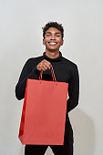 Smiling young african american boy holding red packet