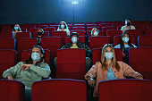 People wearing face masks for protection from virus disease while watching movie in cinema auditorium