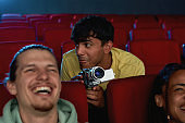Portrait of young guy using his video camera for recording a pirated movie at the cinema
