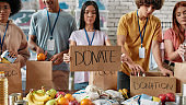 Cropped shot of group of diverse young volunteers packing food and drinks donation, Woman holding card with Donate lettering, Fruits, tin cans and packages on the table