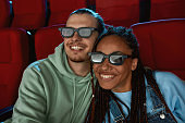 Portrait of lovely couple wearing 3d glasses smiling while watching a comedy together in cinema auditorium