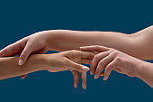 Close up of two female arms holding each other to symbolize taking care isolated over blue background