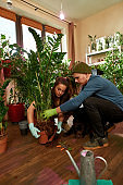 Young caucasian couple taking off old pot from plant