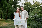 Saving Earth. Young happy couple cleaning together green forest from plastic waste, they holding recycle bin and smiling at camera