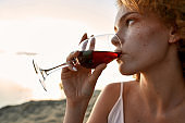 Young caucasian woman drinking red wine from glass